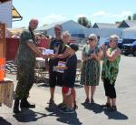 Maj Fenton handing Comox chapter contributions to Marc, Kaitha and their family