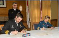 Under the watch of RAdm John Newton, Capt(N) Angus Topshee, Base Commander CFB Halifax, and Col Darlene Quinn, Comd CF RP Ops Gp, sign the real property transfer in Halifax on March 23, 2015. // Sous le regard attentif du Cam John Newton, le Capv Angus Topshee, commandant de la BFC Halifax et le Col Darlene Quinn, Cmdt du Groupe des opérations immobilières des FC, signent le transfert des biens immobiliers à Halifax le 23 mars 2015.