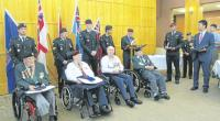 On the right, Kangjun Lee holds the citation in anticipation of presentation while the MC and President of KVA Unit 21, John McDonald reads it aloud. From left to right are: Austin McClure of 59 Independent Field Squadron, Royal Canadian Engineers, William Greeley of 2 PPCLI, Kenneth Storey of the Royal Canadian Medical Corps, and Samuel Frischkent of the Royal Canadian Army Service Corps.