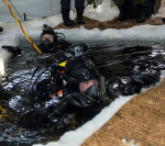 Combat divers during winter training exercise. Here, Sergeant Mathieu Torah, a combat diver with the French armed forces, helps Corporal Pierre-Luc Auger from 5e Régiment de génie de combat, out of the water following an ice dive in Deschambault-Grondines, Quebec on February 19, 2015 during Exercise ROGUISH BUOY. Photo: Cpl Genevieve Lapointe, Valcartier Imaging Section