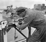 Spr. M.G. Ougler, Second Battalion Canadian Engineers, putting the finishing touches to one of the two new bridges built by the Canadian Engineers. 28 May 1945 / Zutphen, Netherlands. Credit: Canada. Dept. of National Defence/Library and Archives Canada /PA-135997
