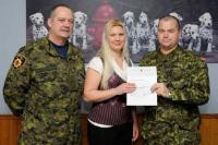 Mrs Nova Fox, wife of Cpl M.R. Fox (Bagotville), receiving the bursary cheque from WO D. Girouard and Sgt P. Calvé.