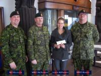 Ashley McPherson,the daughter of MWO J.W. McPherson (Edmonton), receiving the bursary cheque from WO C. Kavanagh, MWO J. McPherson and MWO M. Dumont.