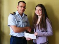 Erin Aucoin, daughter of LCol R.J. Aucoin (Ottawa), receiving the bursary cheque from her father.