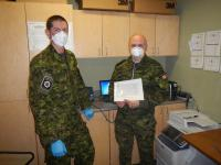 Cpl Milne (left) administers an N95 mask fit test to a member of 8 Wing Trenton.