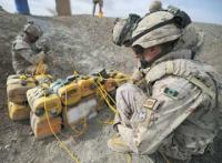 Canadian combat engineers rig improvised explosive devices with C-4 and a detonation cord to dispose of them.
