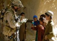 Canadian soldier giving Izzy Dolls to Afghan chidlren