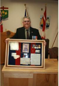 Le Maj Fred Gallant pose avec les documents de service et les médailles de son père. Photo prise par le Cplc Merner, EGMFC