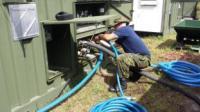 Cpl Sohn, Const Tech, connecting the hoses of the VWR // Cpl Sohn, Tech Const, connectant les boyaux à l'unité de lavage de véhicule
