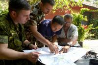 Capt James Borer, a CIMIC officer attached to DART Capt Animesh Adhikari, Nepalese National Army LO, discuss roads status with local authorities. // Le capt James Borer, un officier de CIMIC avec l'EICC le capt Animesh Adhikari, un officier de liaison pour l'armée nationale népalaise, discutent de la condition des routes.