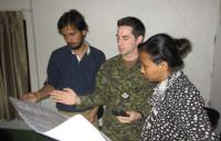 MCpl Denis Carièrre, a DART geomatics technician explains mapping details to Prabhas Pokharel and Megha Shrestha, both volunteers for Kathmandu Living Labs. // Le CplC Denis Carierre, un technicien en géomatique de l'EICC explique les détails du processus de cartographie à Prabhas Pokharel et Megha Shrestha, deux bénévoles des laboratoires vivants de Kathmandu.