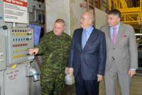 Julian Fantino and James Bezan learn how to operate hangar doors with Sgt Mike Purll, from 402 Sqn at 17 Wing Winnipeg. // Julian Fantino et James Bezan apprennent comment faire fonctionner les portes de hangar avec le Sgt Mike Purll, du 402e Escadron à la 17e Escadre Winnipeg.