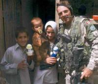 A Canadian soldier‎ in Afghanistan giving Izzy Dolls to children