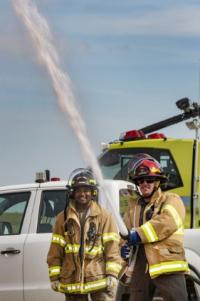 Photo 1 American Vehicle Tech Specialist Heart and the Flight Surgeon Capt Edwards using the fire hose off the KME ARFF Vehicle