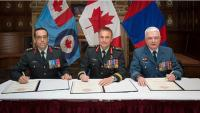 Colonel Martin Gros-Jean, Major-General Sylvain Sirois, and Colonel Kevin Horgan sign Change of Command documents. // Col Martin Gros-Jean, Mgen Sylvain Sirois et ColKevin Horgan procèdent avec la signature des documents officiels pour le changement de commandement.