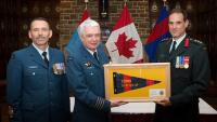 Col Kevin Horgan (centre) receives the Commander's pennant in recognition for his service accompanied by CWO Rémi Nault (left) and Coll Marc Rancourt // Col Kevin Horgan (au centre) reçoit le fanion du Commandant en reconnaissance pour son service , aux côtés de lAdjuc Rémi Nault (gauche) et du Col Marc Rancourt (droite).