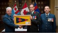 Col Marc Rancourt (centre) receives the Deputy Commander's pennant in recognition of his service, accompanied by Colonel Kevin Horgan (left) and CWO Rémi Nault (right). // Col Marc Rancourt (au centre) reçoit le fanion du commandant-adjoint en reconnaissance de son service, aux côtés du Col Kevin Horgan (gauche) et Adjuc Rémi Nault (droite).
