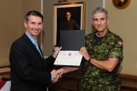 Capt Jacques Landry accepts certificate from MGen Dan Benjamin