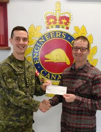 Capt Kevin Elmer from RP Ops Unit West Wainwright presents a bursary cheque to CMEA member WO Raymond Gendron(Ret'd)  on behalf of his son Antoine Gendron who was unable to be present.