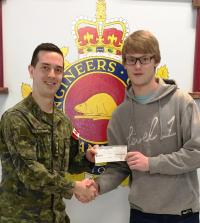 Capt Kevin Elmer presenting a bursary cheque to Matthew Burgess, son of CMEA member Maj Peter Burgess (Ret'd).